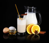 Eggnog with milk and eggs on black background — Stock Photo