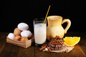 Eggnog with milk and eggs on table and black background — Stock Photo