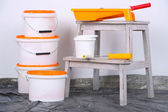 Buckets with paint and ladder on wall background. Conceptual photo of repairing works in  room  — Stock Photo