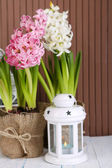 Hyacinth flowers in pots on table on wooden background — Stock Photo