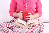 Woman sitting on sofa,  reading book and  drink coffee or tea, close-up — Stockfoto