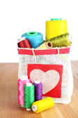 Colorful bobbins of thread  in bag, on wooden  table, on white background — Stock Photo