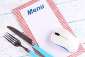 Computer mouse with menu and cutlery on wooden background — Stock Photo