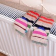 Stock Photo: Knitted gloves drying on heating radiator