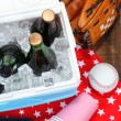 Stock Photo: Ice chest full of drinks in bottles on color napkin, on wooden background