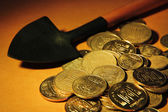 Coins with shovel on brown background — Stock Photo