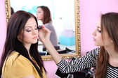 Young woman stylist doing makeup beautiful girl in beauty salon — Stock Photo