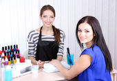 Beautiful girl manicurist doing manicure for woman in beauty salon — Stock Photo