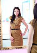 Young beautiful woman standing front of mirror in room — Stock Photo