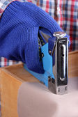 Fastening fabric and wooden box using construction stapler close up — Stock Photo