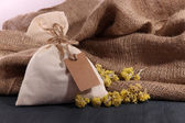 Textile sachet pouch with dried flowers on wooden table, on sackcloth background — Stock Photo