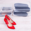 Shoes in plastic boxes and female shoes on floor in room — Stock Photo #42476127