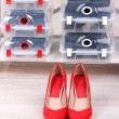 Shoes in plastic boxes and female shoes on floor in room — Stock Photo #42476131