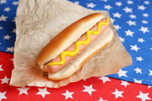 Tasty hot dog on napkin with stars, isolated on white — Stock Photo