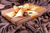 Delicious chocolates in box on brown background — Stock Photo