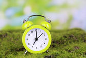 Green alarm clock on grass on natural background — 图库照片