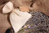 Textile sachet pouch with dried lavender flowers on wooden table, on sackcloth background — Stock Photo