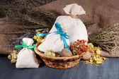 Textile sachet pouches with dried flowers, herbs and berries on wooden table, on sackcloth background — Stock Photo