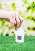 Little paper house in hand close-up, on green grass, on bright background — Stock fotografie