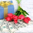Gift boxes with money and flowers on color wooden background — Stock Photo