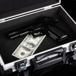 Case with money and gun, isolated on black — Foto Stock