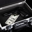 Case with money and gun, isolated on black — Stock Photo