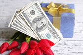 Gift box with money and flowers on color wooden background — Stock Photo