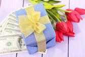 お金と木製の背景の色の花とギフト ボックス — ストック写真