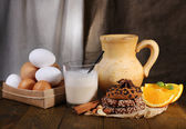 Eggnog with milk and eggs on table and fabric background — Stock Photo