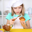 Little girl decorating cupcakes in kitchen at home — Stock Photo #42598041
