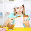 Little girl decorating cupcakes in kitchen at home — Stock Photo