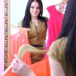 Young beautiful woman trying dresses front of mirror in room — Stock Photo #42599711