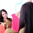 Young beautiful woman trying dresses front of mirror in room — Stock Photo #42599781