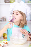 Little girl eating cream in kitchen at home — Stok fotoğraf
