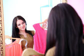 Young beautiful woman trying dresses front of mirror in room — Stock Photo