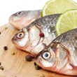 Fresh fishes with lime, parsley and spice on wooden cutting board isolated on white  — Stock Photo #42602965