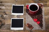 Samenstelling met koffiekopje, decoratieve harten, kruiden en oude foto's in het lege, op houten achtergrond — Stockfoto