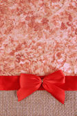 Sackcloth with color ribbon and bow on color paper background — Stock Photo