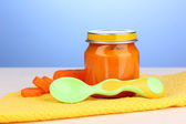Jar of baby puree with spoon on napkin on blue background — Stock Photo