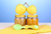 Jars of baby puree with spoon on napkin on blue background — Stock Photo