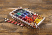 Colourful watercolors and brushes on wooden background  — Stock Photo