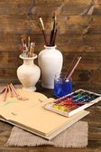 Composition with colorful watercolors, brushes in vase and sketcher on wooden background  — Stock Photo