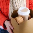 Woman holds box with coffee and cookies close-up — Stock Photo