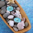 Wooden bowl with Spa stones, sea shells and candles on color background — Stock Photo #42759441