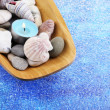 Wooden bowl with Spa stones, sea shells and candles on color background — Stock Photo #42759449