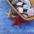 Wooden bowl with Spa stones, sea shells and candles on color background — Stock Photo #42759467