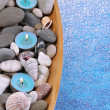 Wooden bowl with Spa stones, sea shells and candles on color background — Stock Photo #42759469