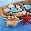 Wooden bowl with Spa stones, sea shells and candles on color background — Stock Photo #42759477