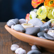Composition with spa stones and candles in wooden bowl, near flowers on bright background — Stock Photo #42759523
