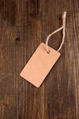 Brown tag on color wooden background — Stock Photo